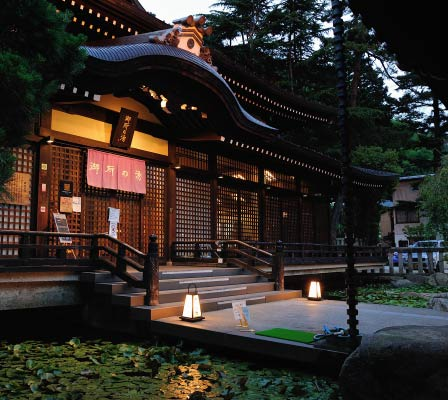 Goshonoyu Onsen's exterior entrance at sundown. Lilypads cover the small ponds to either side of the entrance.