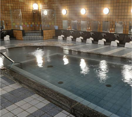 The large interior washroom of Jizoyu Onsen, it has tiled floors and walls and also baths.