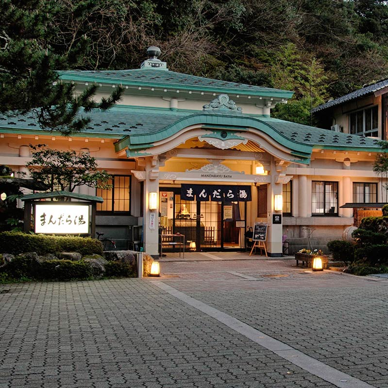 The exterior of Mandara-yu Onsen at twilight, with it's green tiled roof and moody exterior lighting.