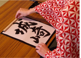 A woman writing 'Kinosaki Onsen' in Japanese characters, in the traditional art of Japanese calligraphy