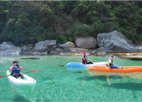 A group of three kayaks floating on the pristine waters of Takeno beach