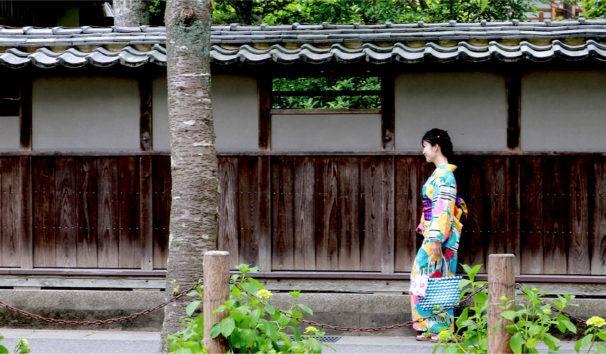 A woman in colorful Yukata strolling past a traditional Japanese manor wall