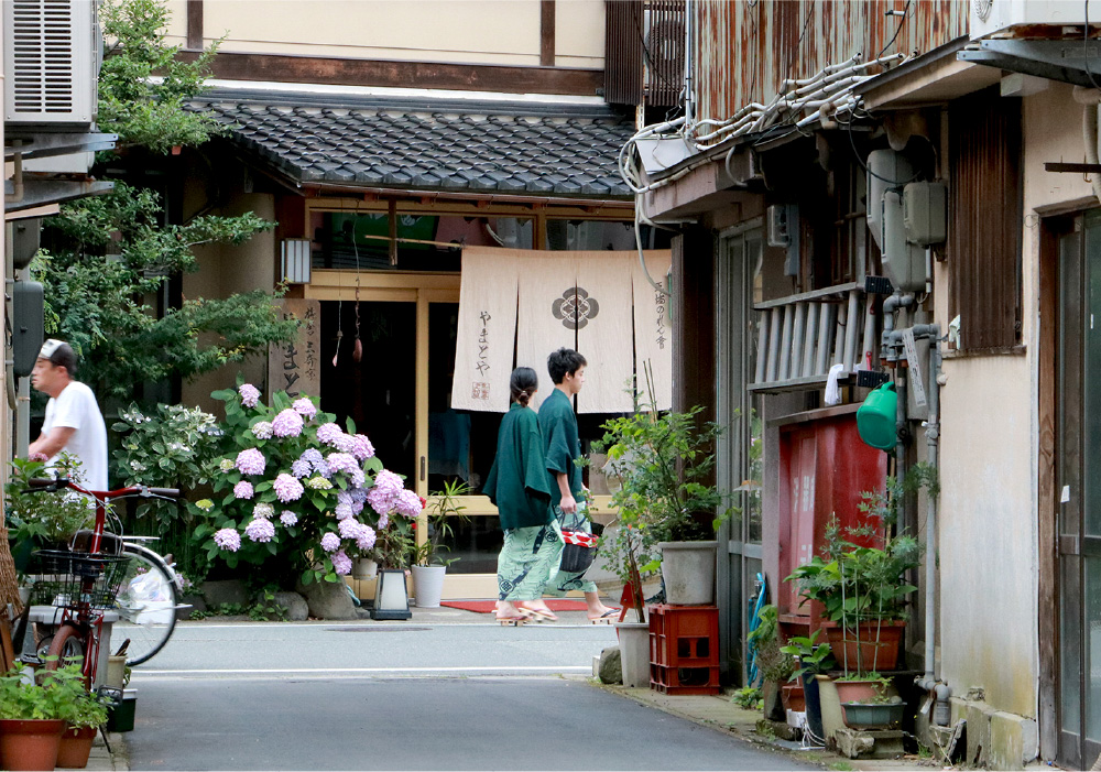 The back alley of Kinosaki. Traditional wooden styled buildings and blooming flowers