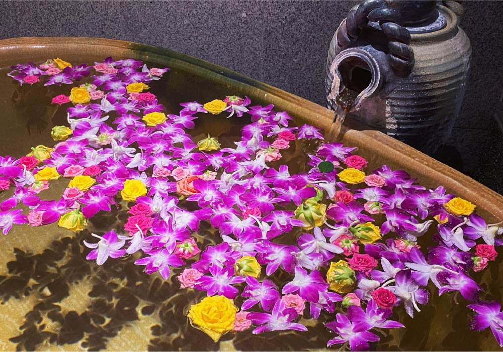 A private ryokan bath, filled to the brim and complete with colorful flowers floating above the water