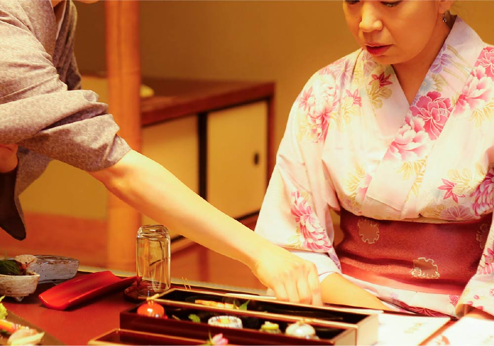 A woman in a colorful pink floral yukata sitting, being served her meal by ryokan staff