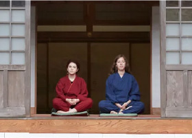 Two foreign woman sitting in pentive cross-legged poses on the veranda of a temple