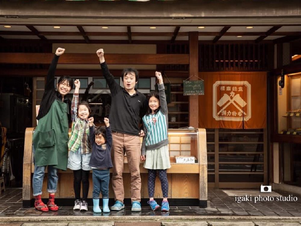 The owners of Chikara Mochi restaurant and their family all raising one of their hands in a fist, as if to say 'power!'. ('Chikara' means power in Japanese, and Mochi is a type of rice cake)