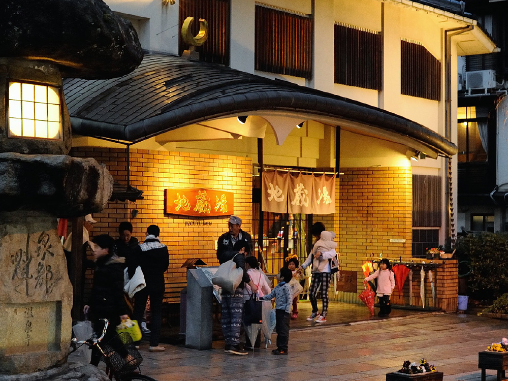 The exterior of Jizoyu Onsen, with many people waiting around outside