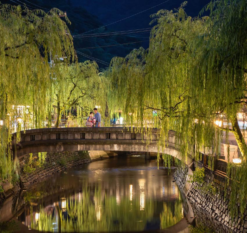 The willow lined river of Kinosaki Onsen town. A stone bridge straddles the river