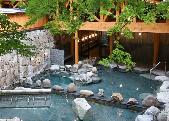 Goshonoyu Onsen's open and expansive outdoor baths. Maple tree branches hang over the pools.