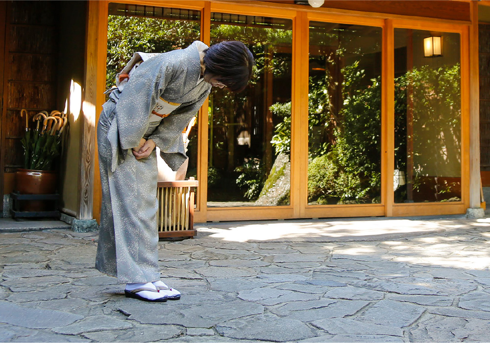 Ryokan staff bowing in farewell to guests as they leave