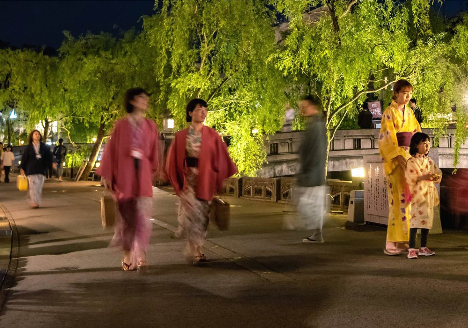 People walking the willow-lined streets of Kinosaki Onsen in their colorful Yukata at night
